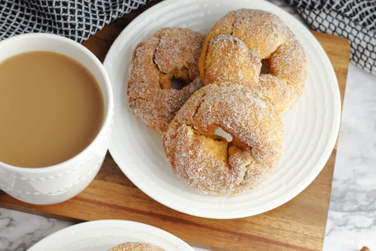 pumpkin donuts on plate with coffee mug